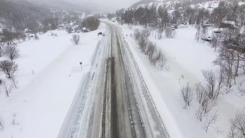Aerial View of a Winter Road in a Snowy Day.