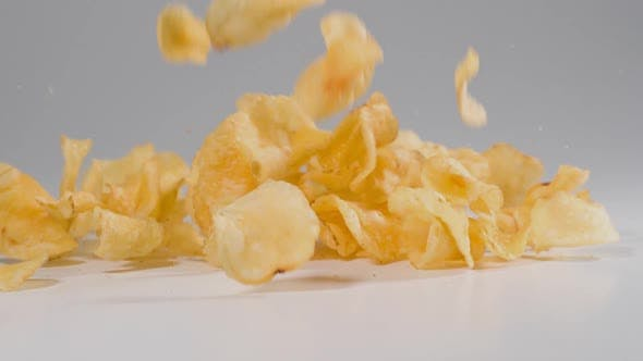Thumbnail for Potato Chips falling onto a white surface in slow motion