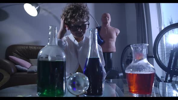 Thumbnail for Little Boy in Eyeglasses and Lab Coat Looking at Flasks Filled with Chemicals and Thinking