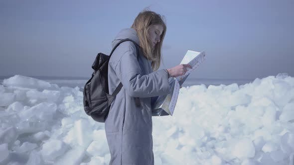 Attractive Blond Woman with Backpack Checking the Map in Front of Ice at the North or South Pole