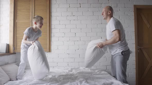 Thumbnail for Happy Little Boy and his Father Pillow Fighting in Morning