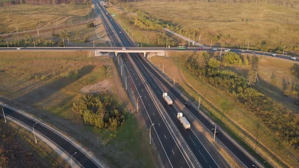 Cover Image for Aerial View. Interchange on the Intercity Highway. Cars and Trucks Travel in Different Directions