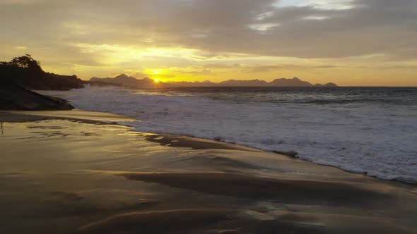 Slow motion, static shot of waves flowing in from the ocean on Ipanema beach at sunset