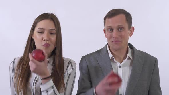 Cover Image for Portrait of Man and Woman Eating Apples and Smile Isolated on White Background