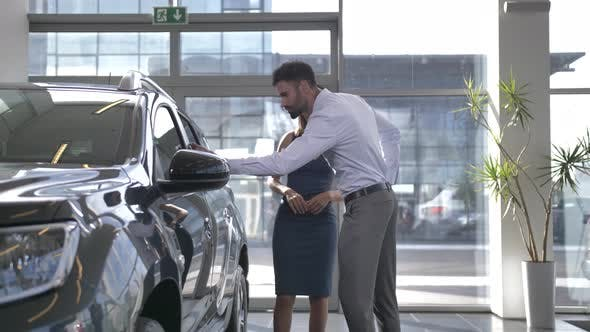 Couple Interested in Buying New Car at Dealership
