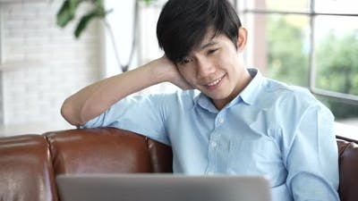 young Asian person working business on laptop at home, businessman working from home on cyberspace