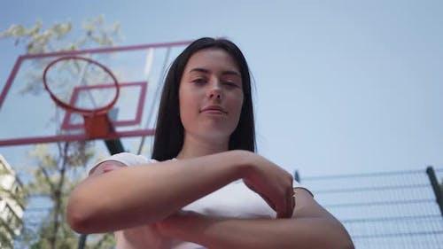 Porträt Niedlich teen Brünette Mädchen wirft ein Basketballball in den Ring Blick auf die Kamera stehend