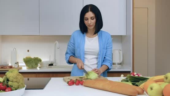 Thumbnail for Woman which Cutting Cabbage with Knife on Cutting Board in the Kitchen and Looking at Camera
