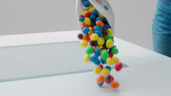 Multiple Colourful Candy Being Dropped on Table