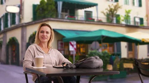 Attractive woman sitting outside cafe