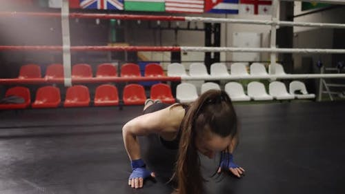 Female Boxer in Boxing Bandages Doing Push Ups While Training in Boxing Ring