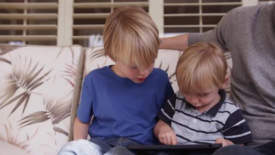 Thumbnail for A cute young white boy playing on a tablet with family