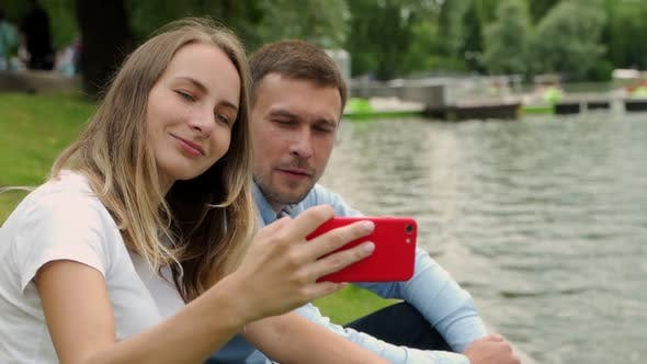 Thumbnail for Young Couple Taking Self Portrait By a Lake. Man and Woman on Vacation in Taking Selfie with Their