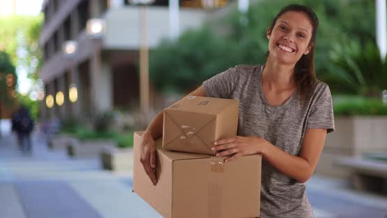 Beautiful Caucasian girl on college campus holding care package from family