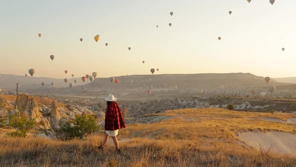 Woman in a hat walking in Cappadocia. Colorful hot air balloons flying over the valley