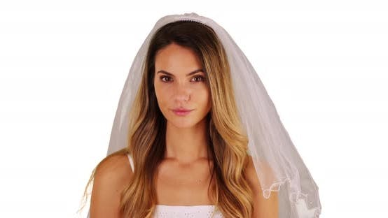 Thumbnail for Close up of bride in white dress and veil standing in studio with copy space