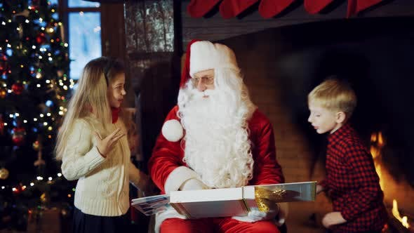 Thumbnail for Santa Claus is Sitting in the Middle of a Room with an Album in His Hands Surrounded By Children
