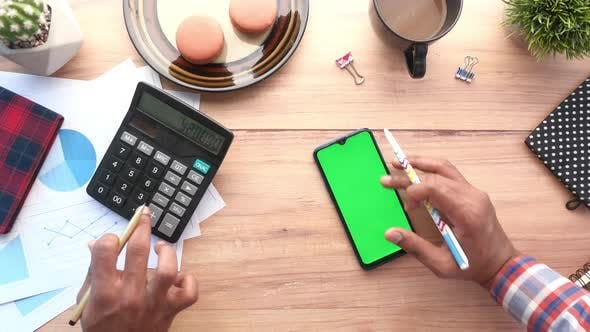Hand Using Smart Phone and Calculator on Table  Top Down