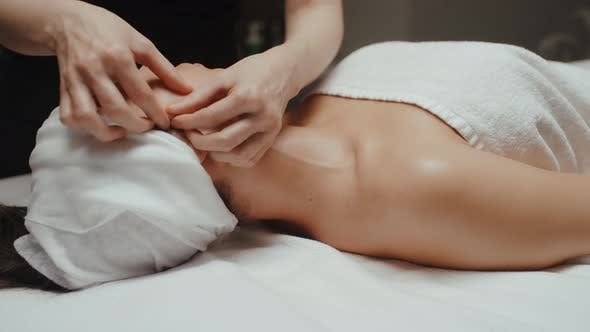 Thumbnail for Woman Receiving Facial Massage in Spa Lying on Massage Table. Wellness Body and Skin Care