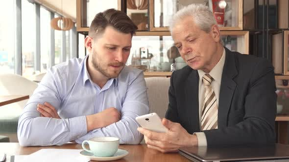 Thumbnail for Senior Businessman Shows His Partner Something on His Smartphone