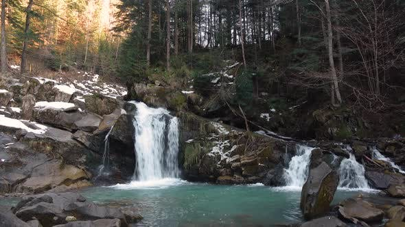 Thumbnail for Mountain Waterfall with Turquoise Water Among the Snowy Stones and Forest, Carpathians in Winter.
