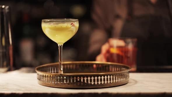 Bartender with Glasses of Cocktails at Bar