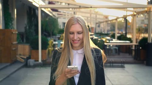 Formal Business Woman Walking on Street. Elegant Blond Young Woman in Suit and Walking on Street and