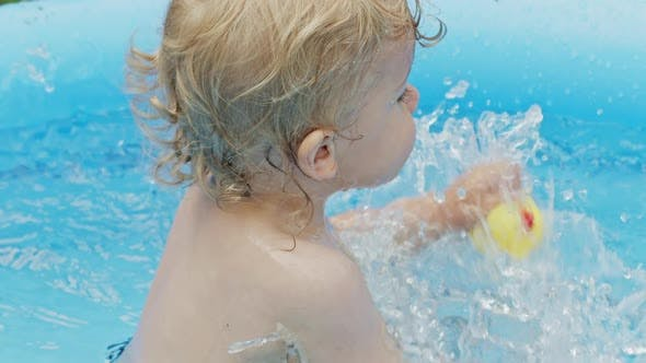 Adorable Little Baby Swimming in Blue Street Pool in Courtyard. Portrait of Joyful Toddler. Kid