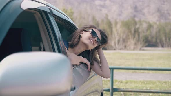 Thumbnail for Lady in Sunglasses Fixes Hair Leaning Out of Car at Field