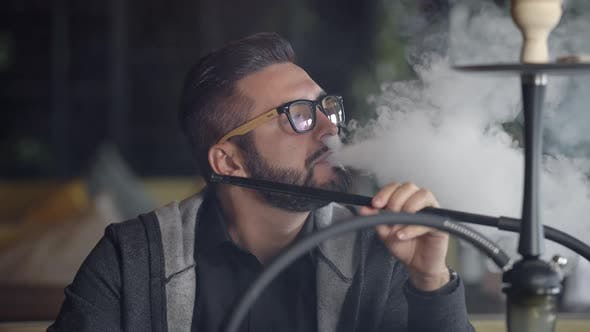 Thumbnail for Close Up Shot of a Stylish Adult Guy Smoking Hookah Indoor of a Cafe Alone