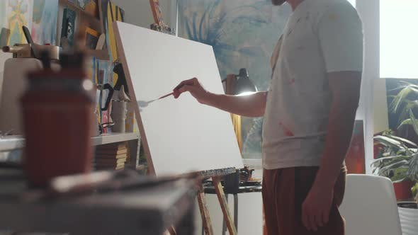 Creative Man Drawing Picture on Canvas in Art Studio