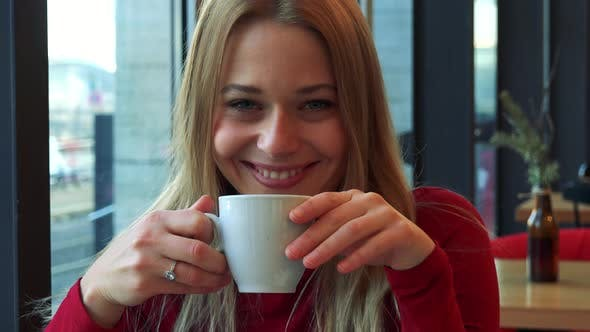 Thumbnail for A Young Attractive Woman Sits at a Table in a Cafe, Drinks Tea and Smiles at the Camera - Closeup