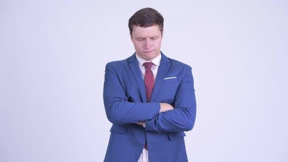 Stressado jovem empresário olhando irritado com braços cruzados de ...