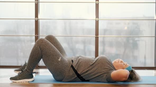 Fette Frau macht Crunches im Fitnessstudio