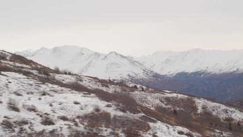 Lufthubschrauber über verschneite Alaska-Berge in der Dämmerung, Drohne aufnahmen