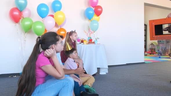 Animator zeigt magischen Trick mit leerer Box auf Geburtstagsfeier