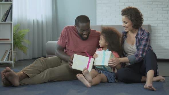 Thumbnail for Niedlich kleines Mädchen erhalten Geschenke von Eltern für ihren Geburtstag im Wohnzimmer