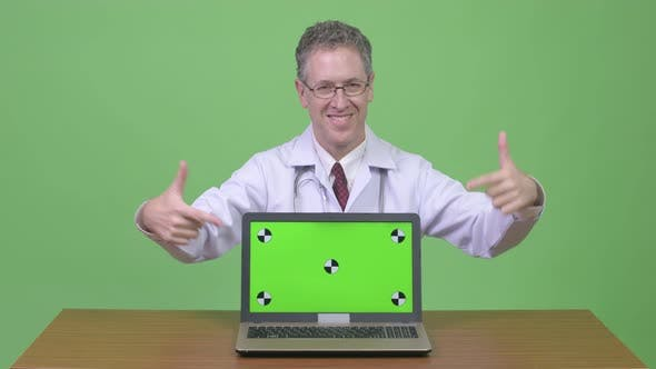 Thumbnail for Happy Mature Man Doctor Showing Laptop and Giving Thumbs Up Against Wooden Table