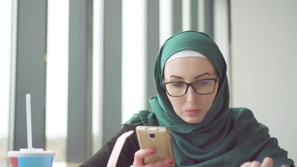 Young Muslim Woman in a Hijab Is Sitting at a Table By the Window Using the Phone and Eating