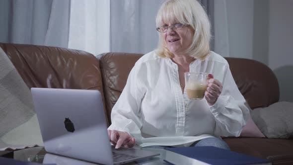 Thumbnail for Positive Caucasian Senior Woman in Eyeglasses Sitting at Couch with Coffee and Surfing Internet