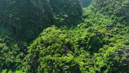 Aerial: North Vietnam karst landscape at sunset, drone view of Ninh Binh region, tourist destination