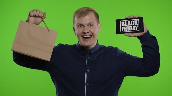 Man Showing Shopping Bags and Black Friday Inscription, Looking Astonished By Low Cost Purchase