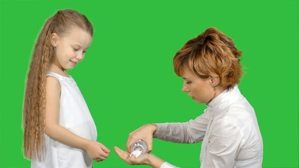 Cover Image for Mother giving her daughter medicine on a Green Screen, Chroma Key