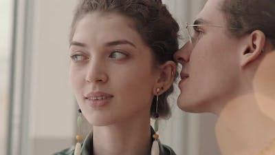 Joyful Man Whispering in Woman Ear