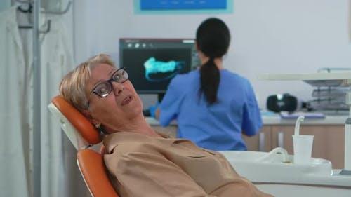 Senior Woman Looking on Camera Waiting on Dental Clinic