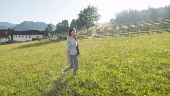 Thumbnail for Girl Walking in a Field Near an Alpine Village
