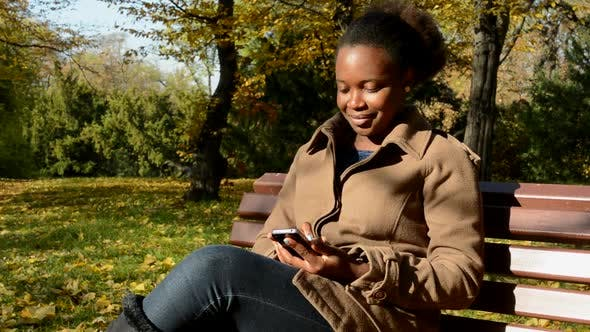 Cover Image for Young Beautiful African Happy Girl Sits on Bench in Woods, Works on Phone and Observes Landscape