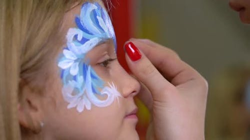 Artist's Hand Glueing Rhinestones on the Kid's Face. Close-up Motion