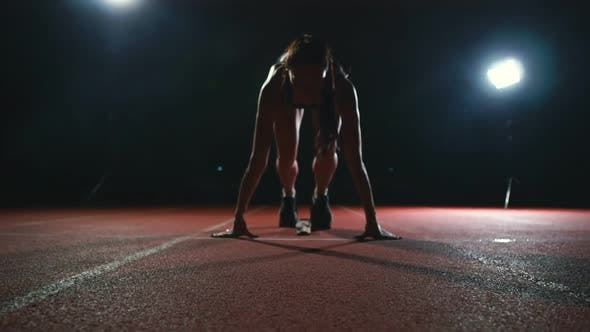 Thumbnail for Athlete Woman in Black Shorts and a T-shirt in Sneakers Are in the Running Pads on the Track