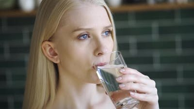 Woman Drinking Water From a Glass Indoors